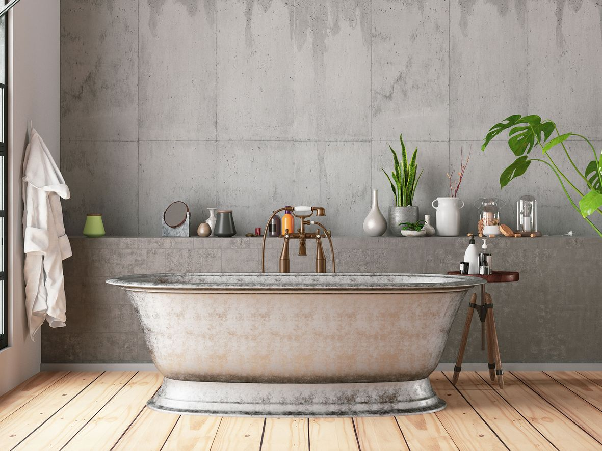 Grey bathroom with concrete walls, a stainless steel bath and wooden floor