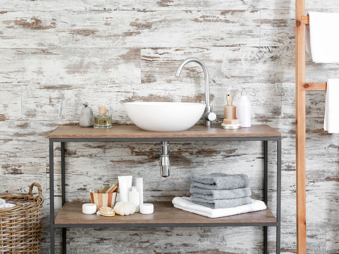 Wooden bathroom sink unit in a bathroom with white-washed brick wallpaper and a bathroom storage ladder