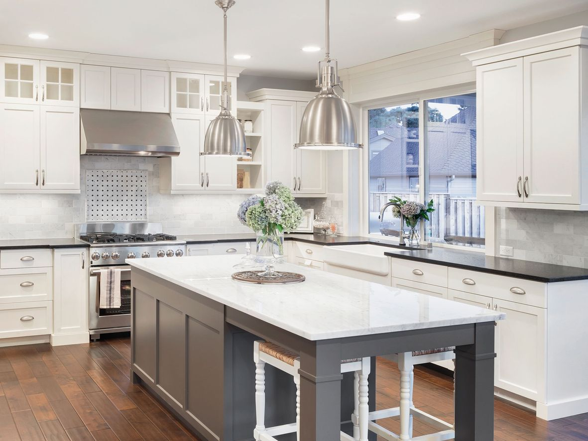 White traditional kitchen with a grey kitchen island with seating stored underneath