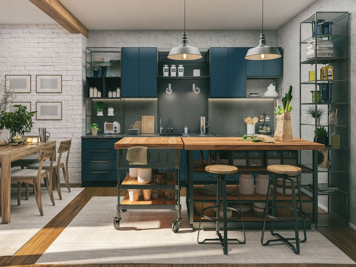 Freestanding kitchen island with a wooden worktop in an open-plan blue kitchen