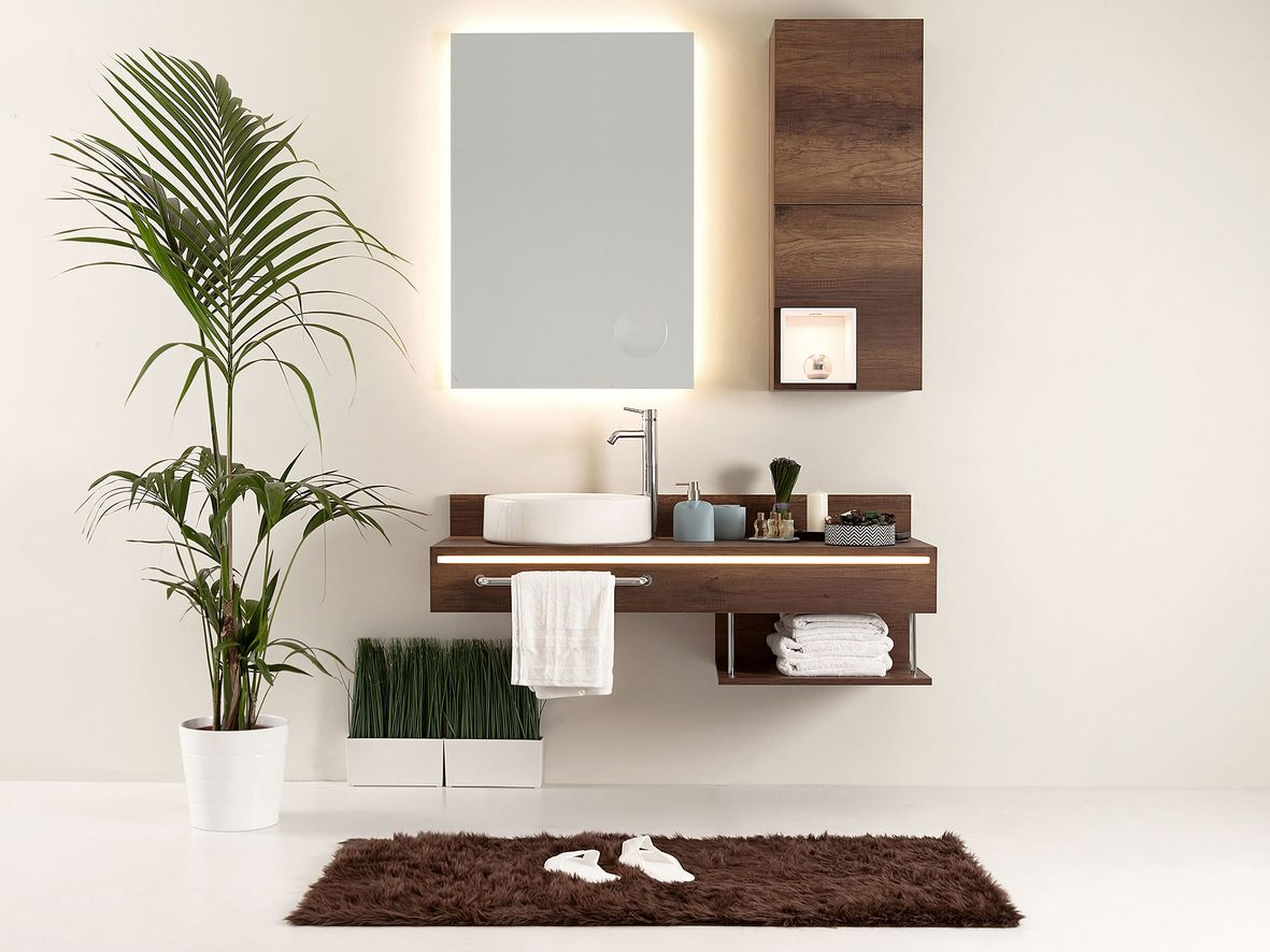 Dark wood bathroom sink unit with rails to hand towels and thin wall cabinet next to a mirror with lights around it