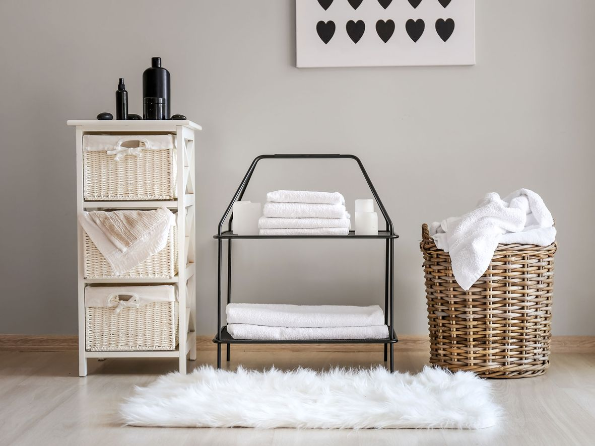 White wicker bathroom basket unit next to low-level black shelves and a round wicker basket