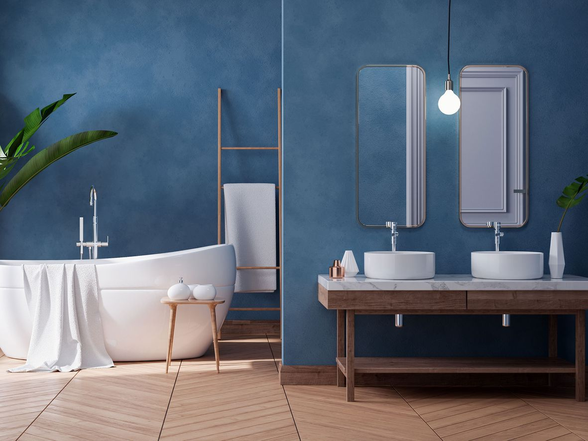 Blue bathroom with stippled paint effect walls, a white oval bath, wooden floating sink unit with two white sinks and mirrors above