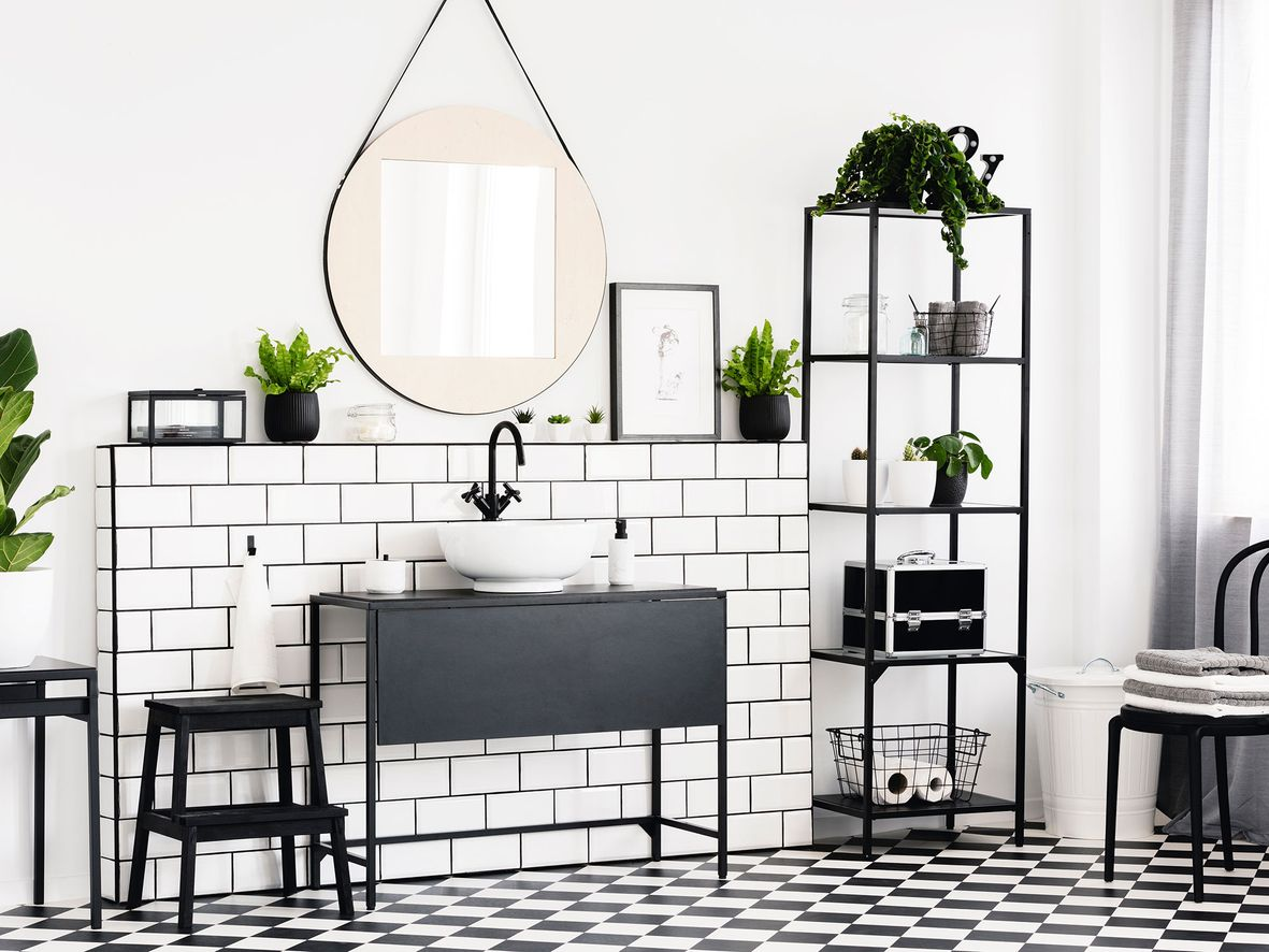 Black and white bathroom with checked floor, white walls, white tiles around a grey freestanding sink unit with a round mirror above it and a black open shelving unit to the side