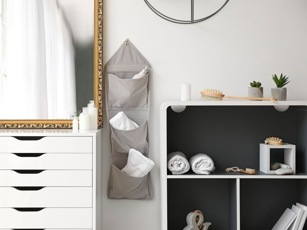 White bathroom drawer unit and shelf unit with a grey storage hanger in between