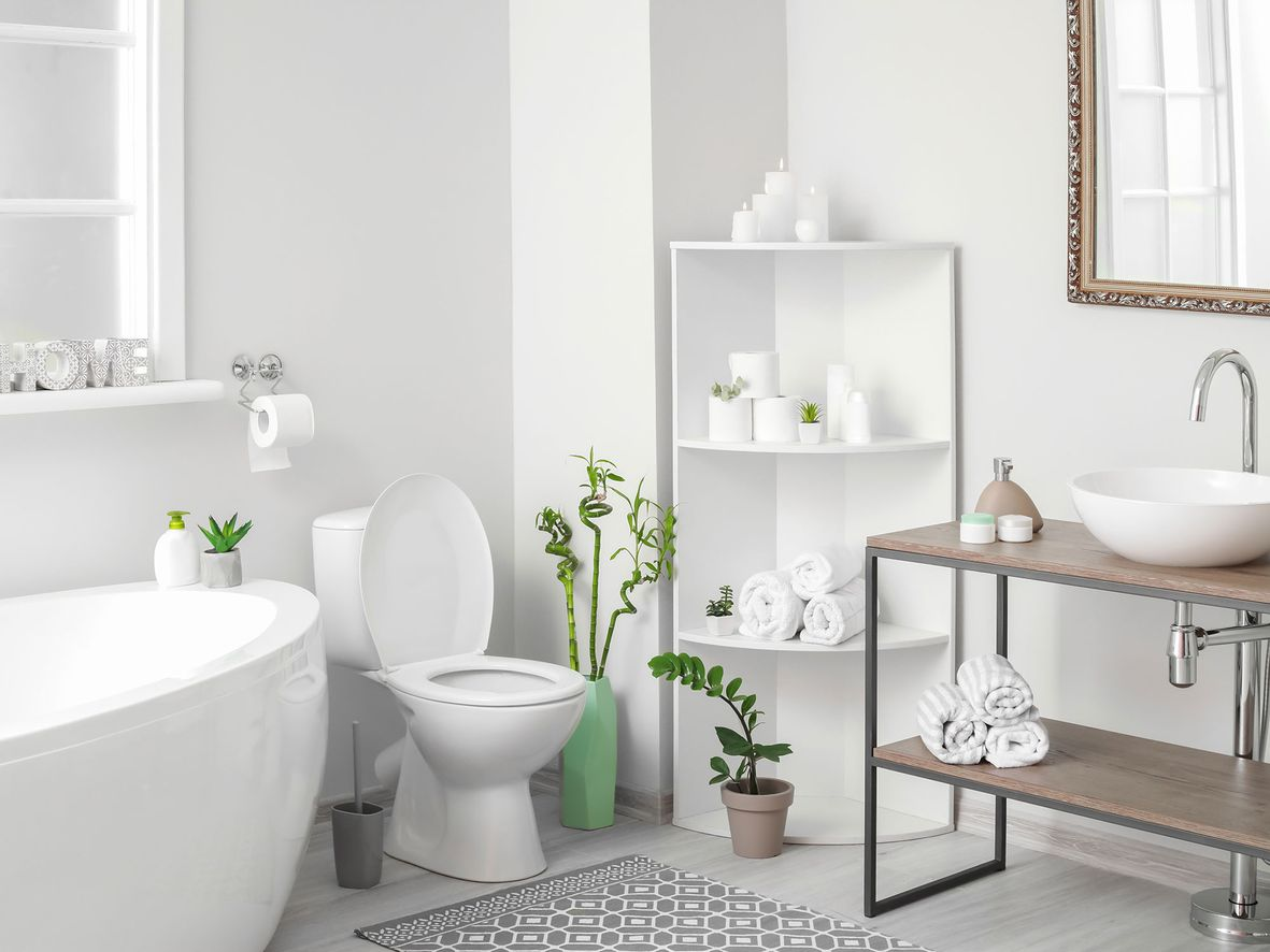 White bathroom corner shelf unit with three shelves in an all-white bathroom with oval bath, toilet and open wood sink unit