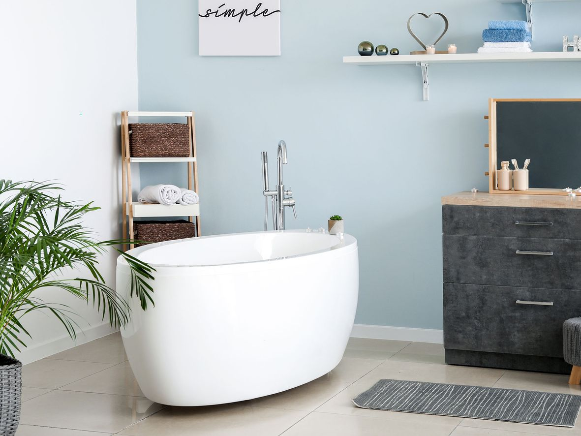 Muted bathroom with one pale blue bathroom wall, black drawer unit, white oval bath and corner shelf unit
