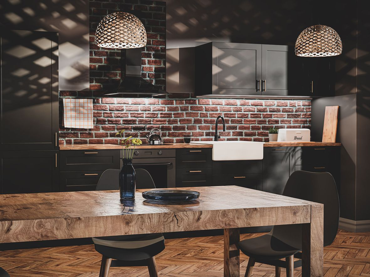 Kitchen with dark units, exposed brick and a wooden table