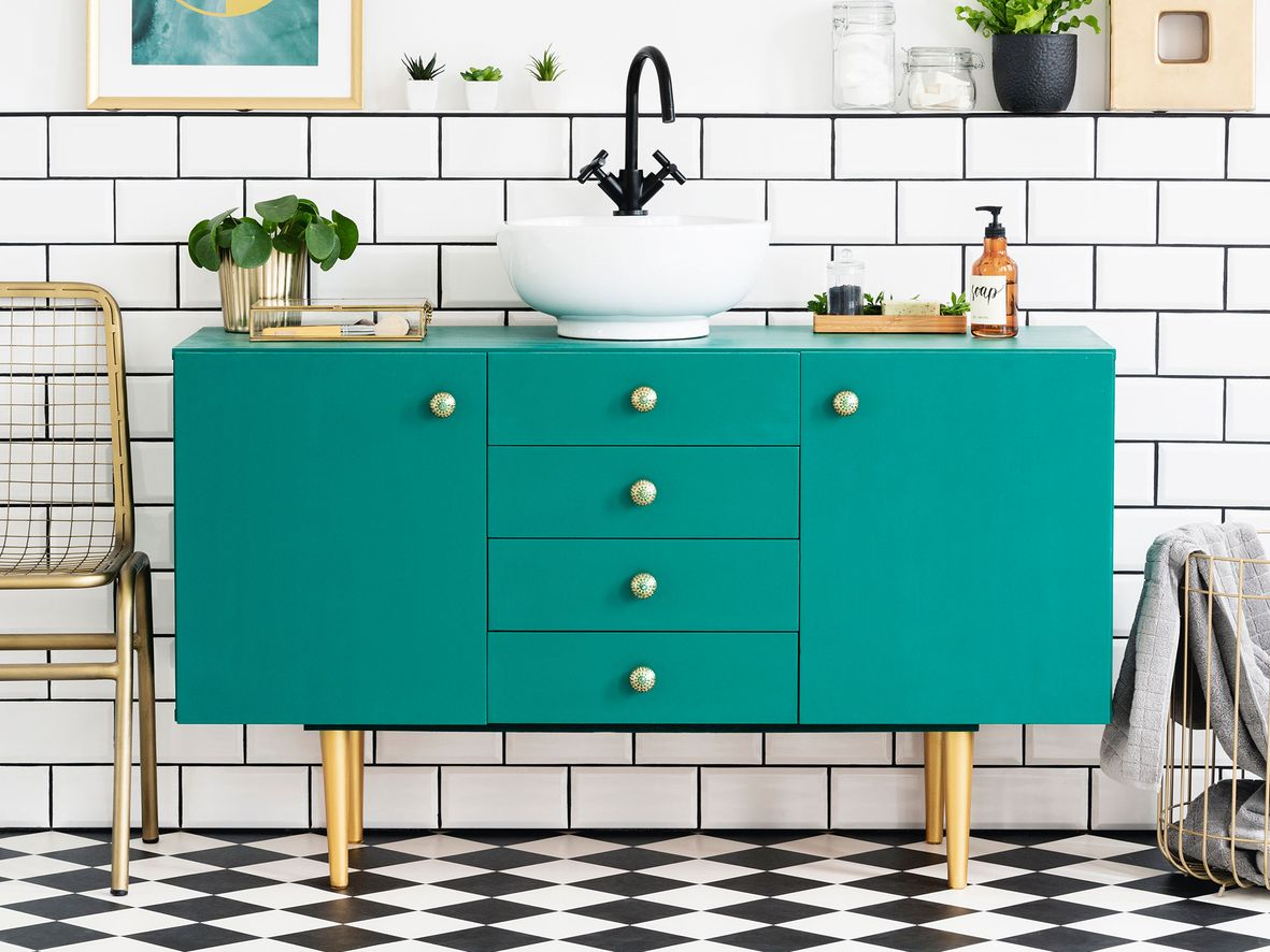 Freestanding bathroom sink unit painted green in a bathroom with white tiles, white sink and black tap