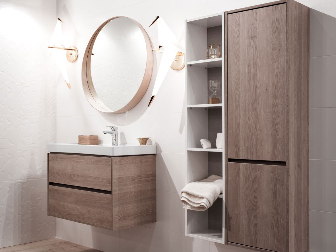 Dark wood bathroom wall unit with a cupboard and shelves and vanity unit below a round bathroom mirro