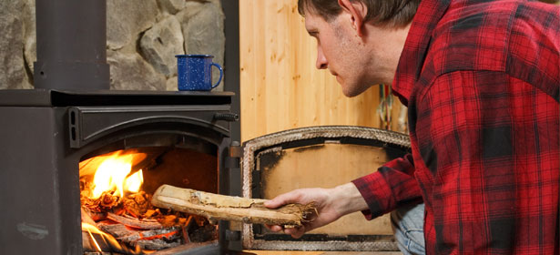 putting a log into a wood burning stove