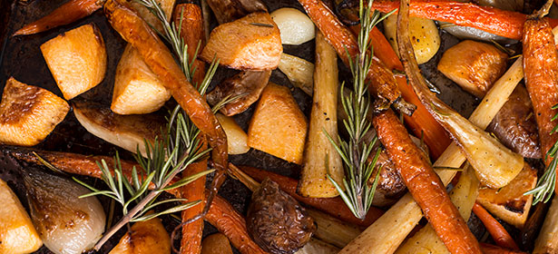 Roasted potatoes, carrots and parsnips with sprigs of rosemary