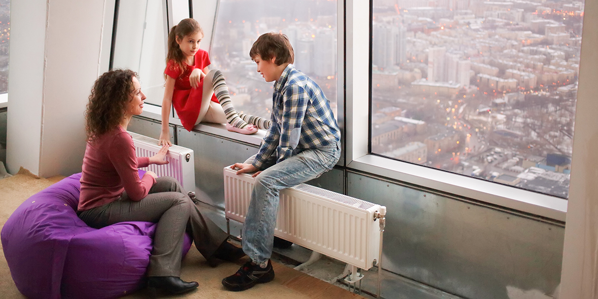 Mother and children sitting beside large radiators