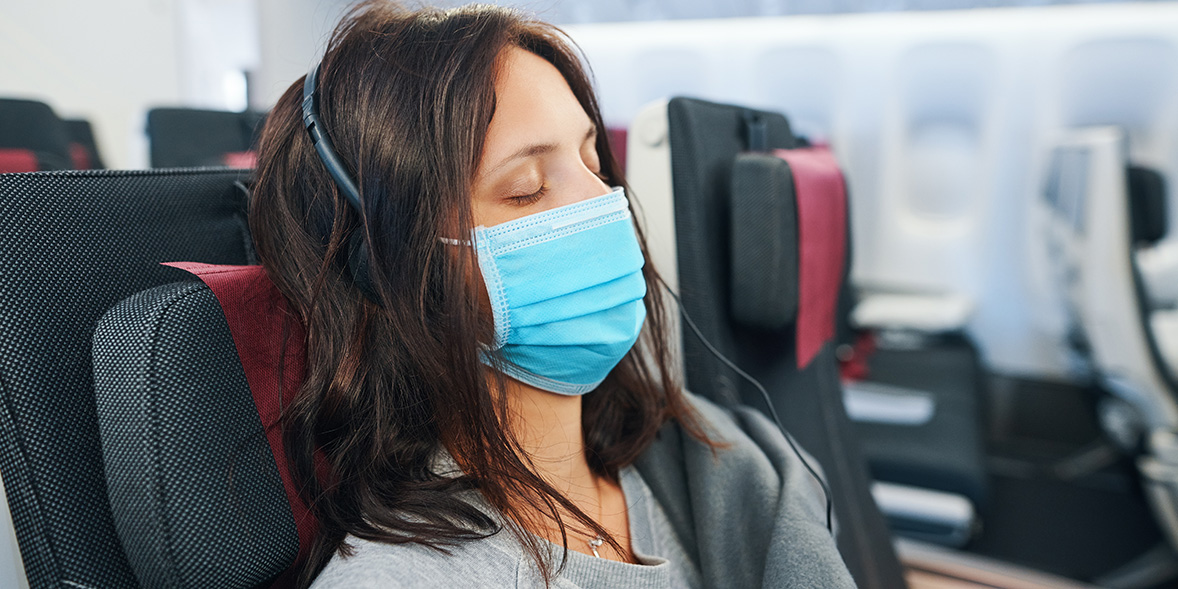 woman wearing face mask on a plane