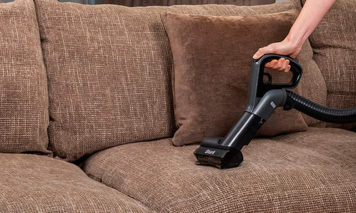 A Shark motorised pet tool being used to clean a sofa