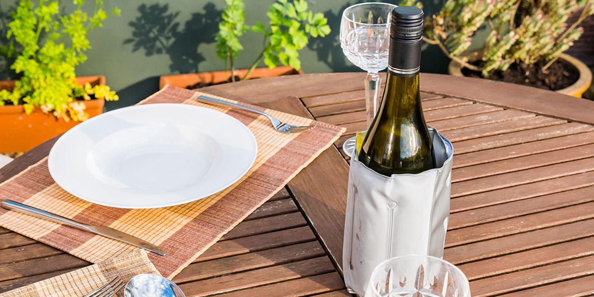 Wine in a wine bottle cooler on outdoor furniture.