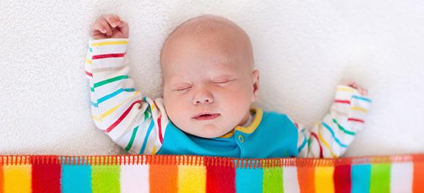 Baby boy asleep under rainbow blanket