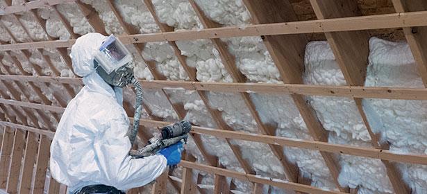 Installer spraying foam insulation into place
