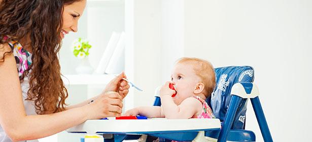Mum feeding baby in high chair