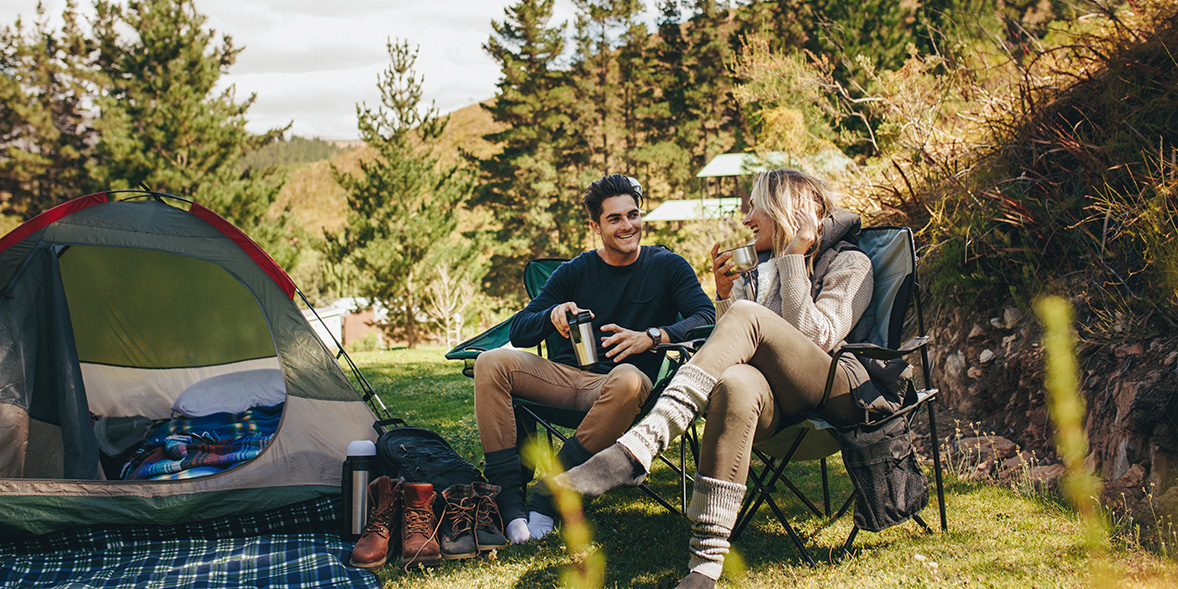 Two people sitting on camping chairs on a camping trip.