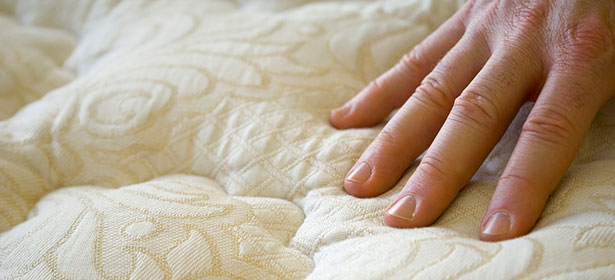 Image of a person's hand pressing down on a mattress to feel the firmness.