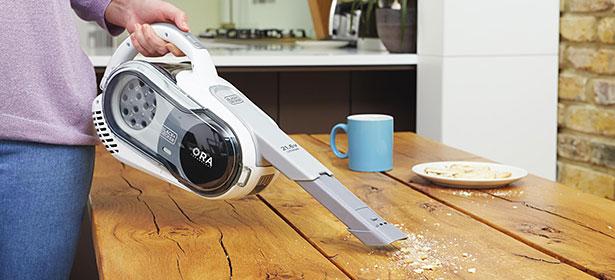 Handheld vacuum used on wood table