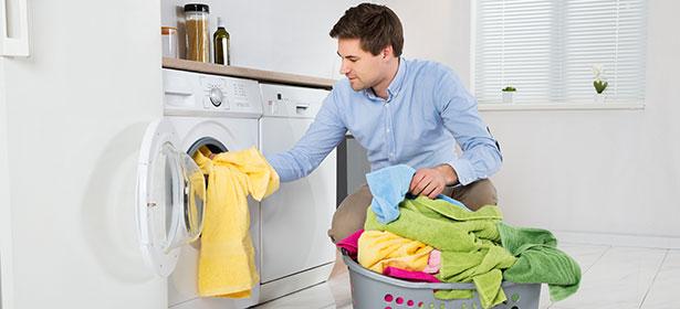 Man loading clothes into washing machine