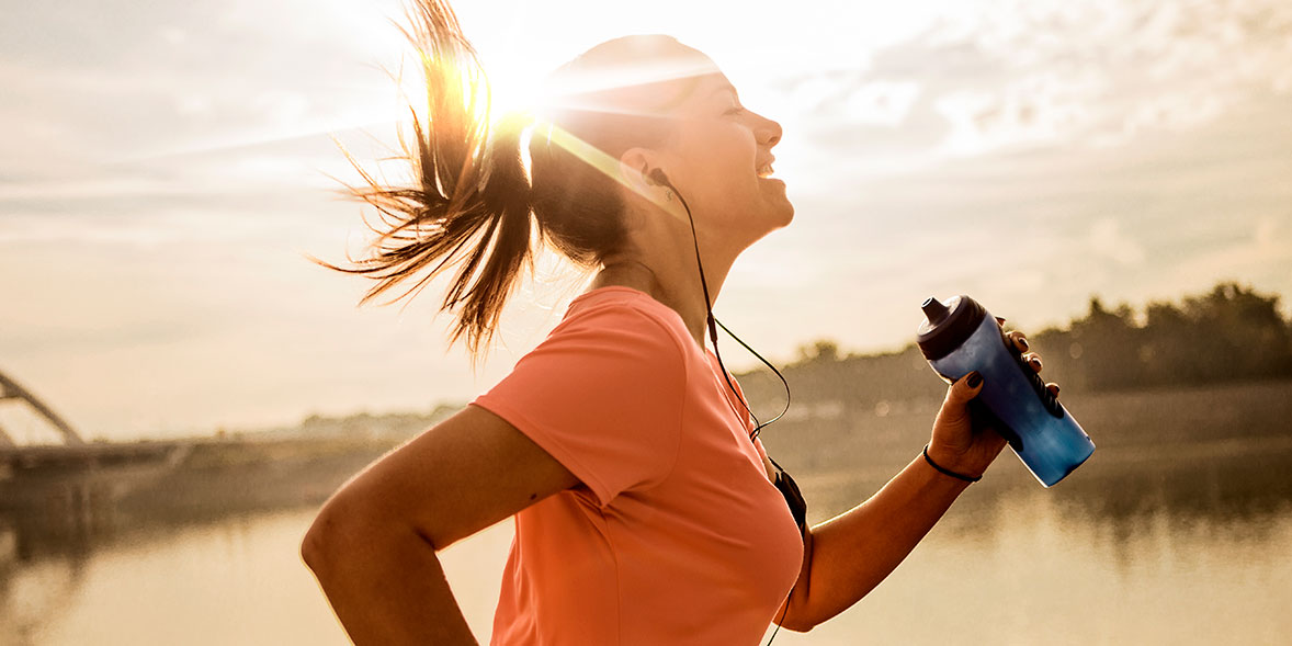 Woman running with a water bottle and headphones