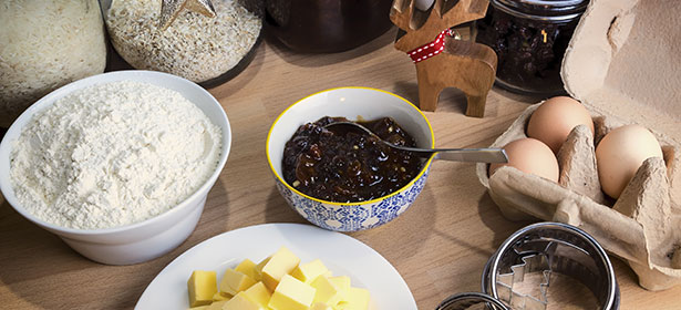 ingredients for making mince pies on table including flour, mincemeat, butter and eggs