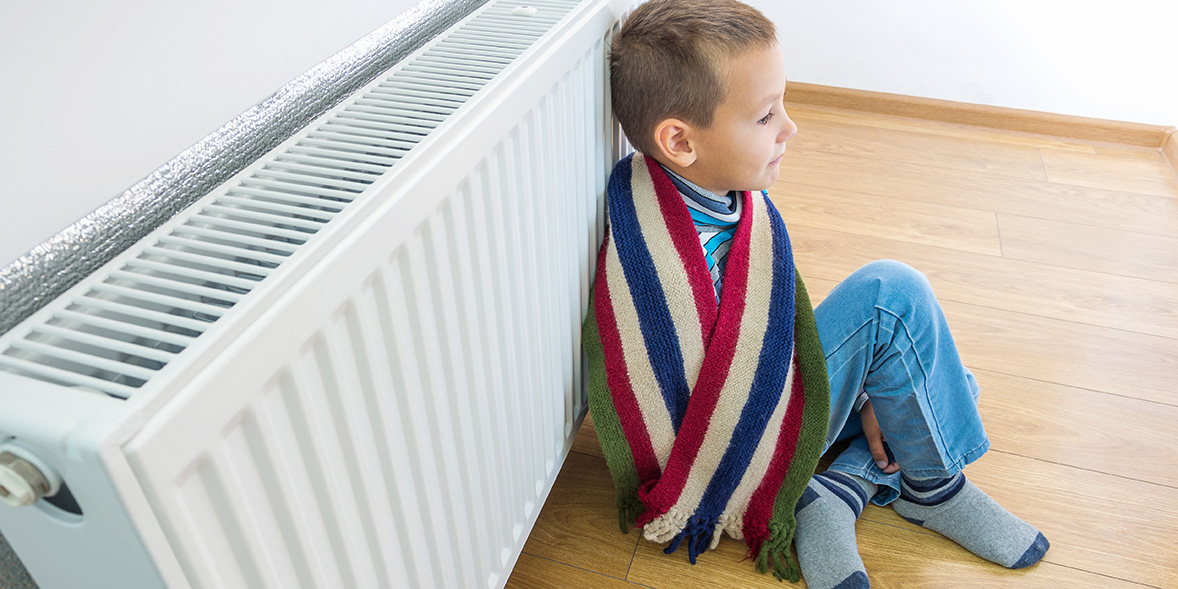 Young boy wearing a scarf, sitting by a radiator