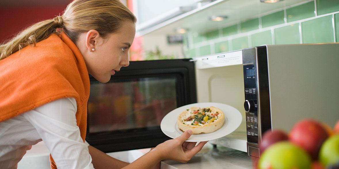 Woman heating food in microwave