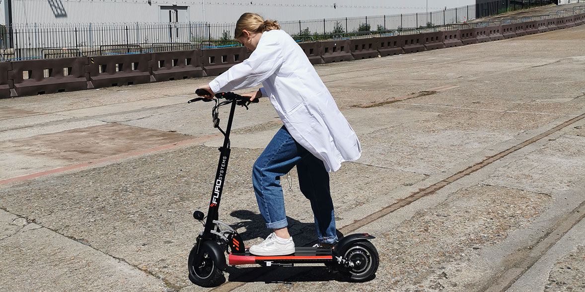 A researcher riding an electric scooter