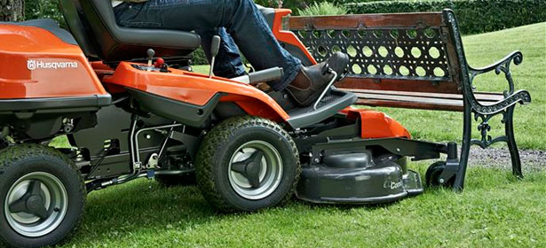 Cutting grass under a bench using a ride-on lawn mower