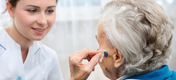 Senior inserting hearing aid 434584