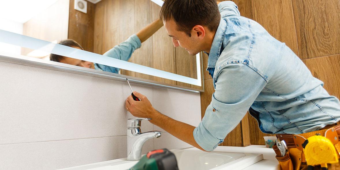 Bathroom fitter installing a bathroom mirror