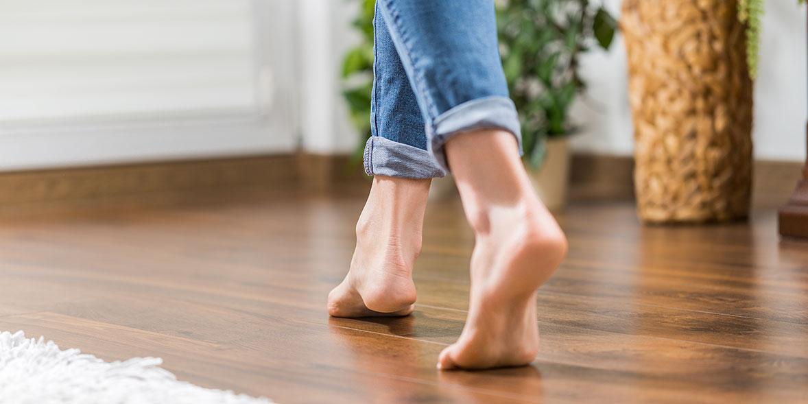 Bare feet walking on a wooden floor with underfloor heating