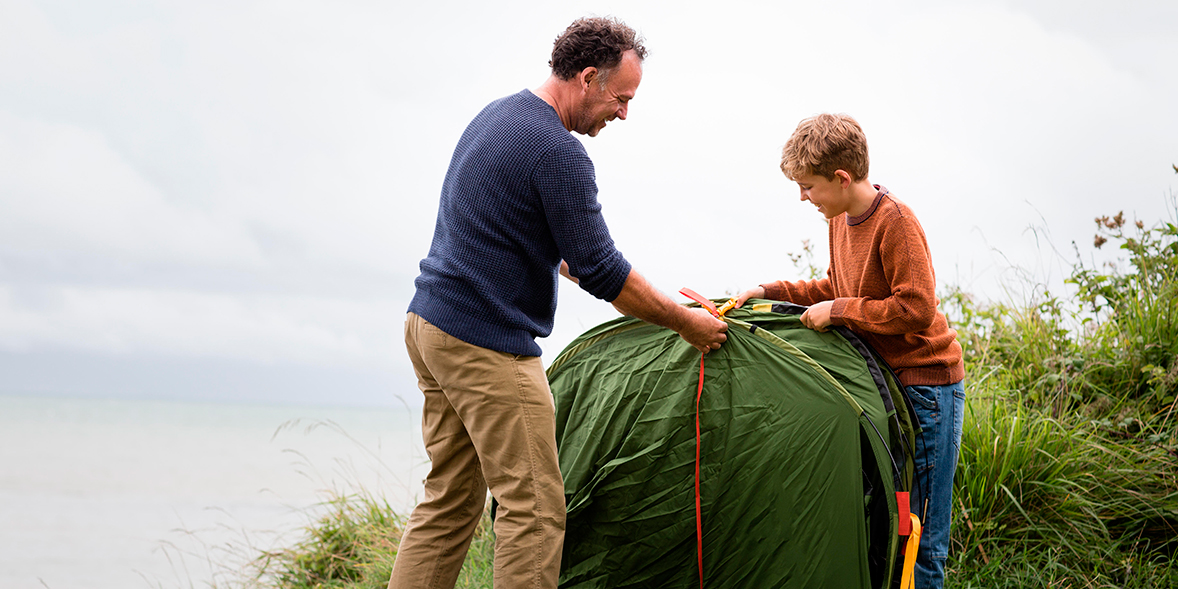 Father and son pitching a pop up tent