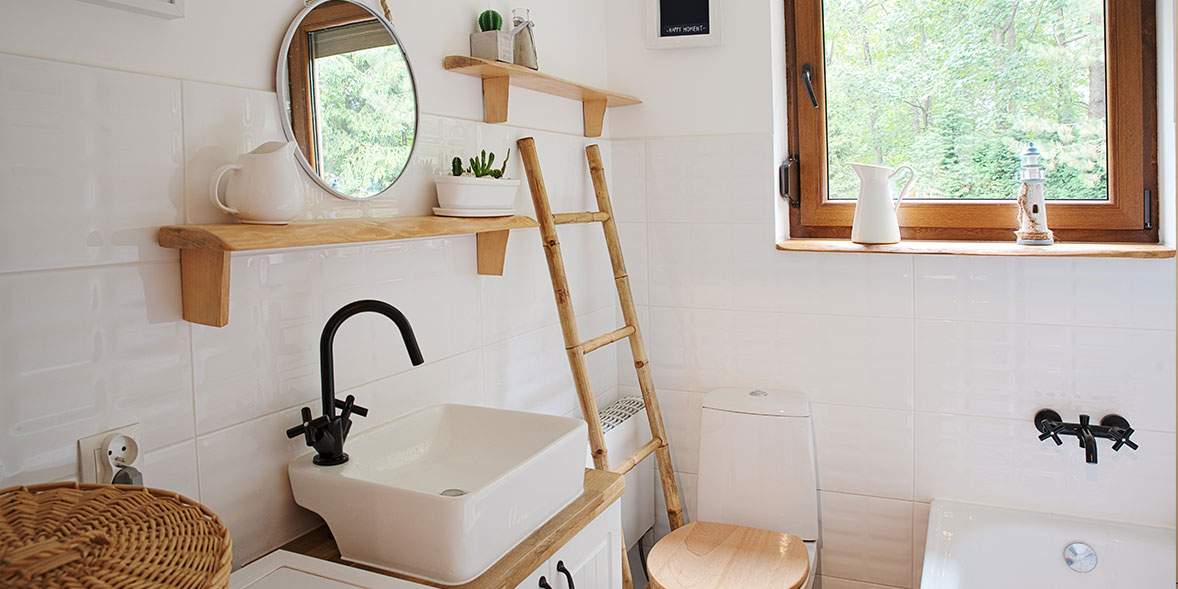 Small bathroom with white wall tiles, wooden shelving and a wooden bathroom ladder shelf