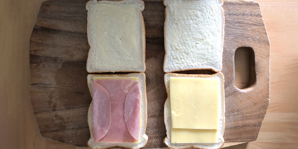 A cheese toastie and ham and cheese toastie being prepared