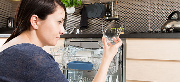 Woman examining a glass cleaned in dishwasher