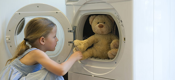 Girl tumble drying teddy bear