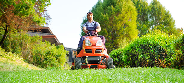 Man driving an orange ride-on lawn mower