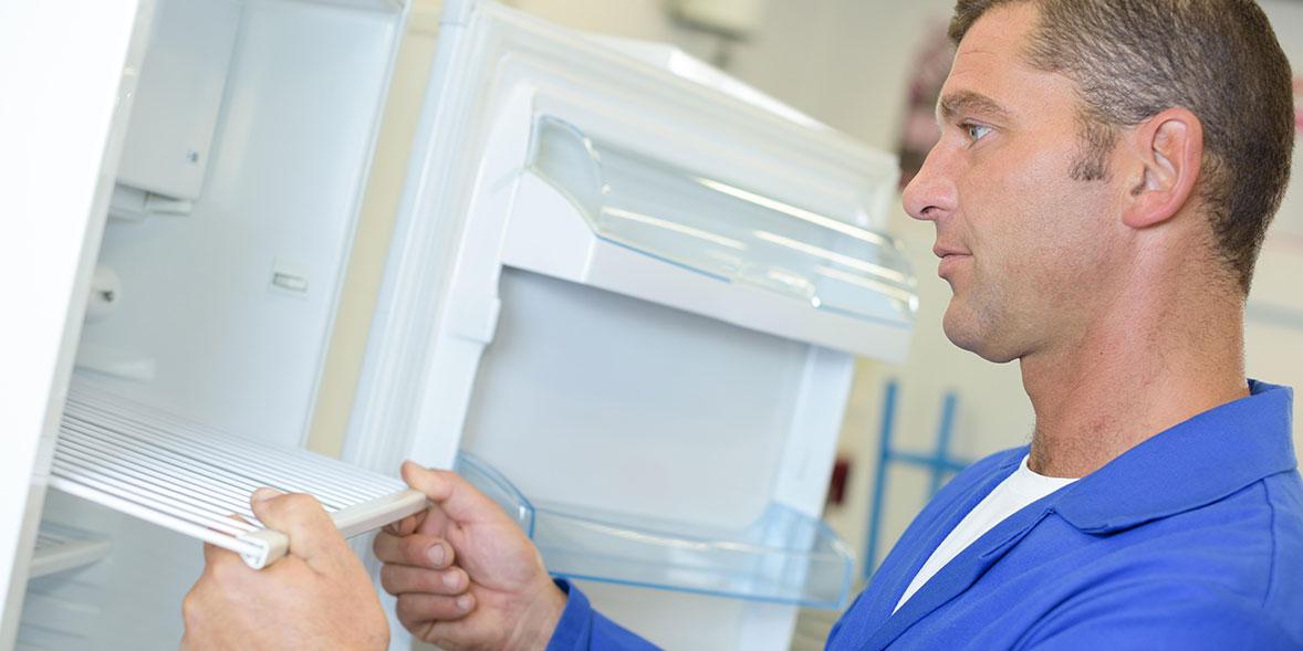 Man replacing fridge shelves