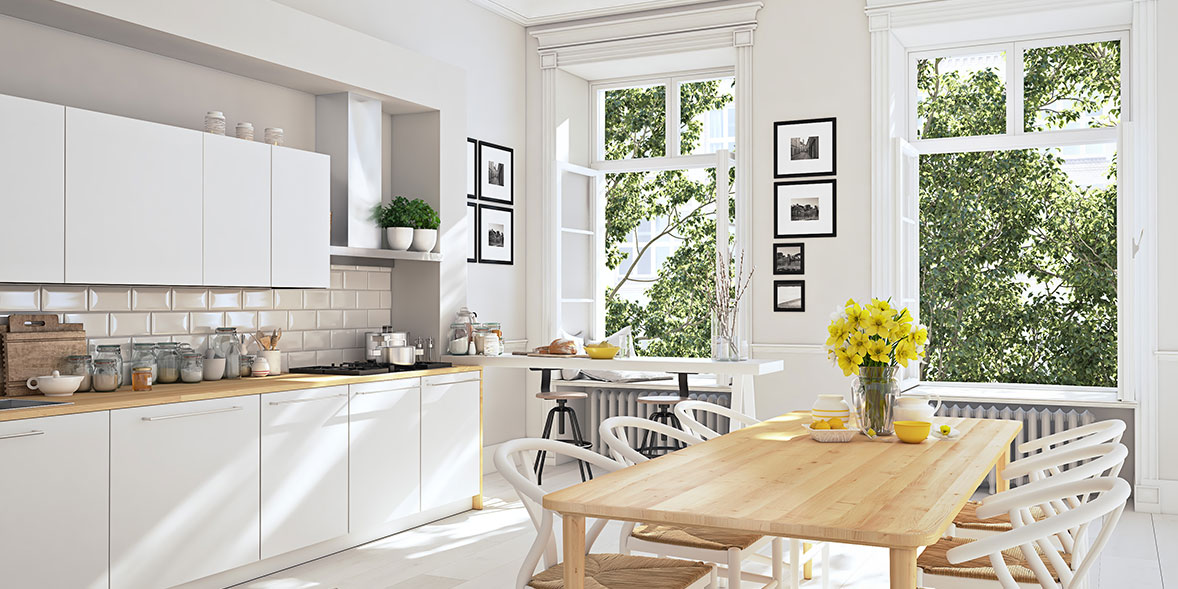 Scandinavian kitchen with white units, wooden worktops and a wooden table