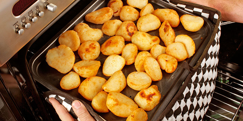 Taking out tray of roast potatoes from oven