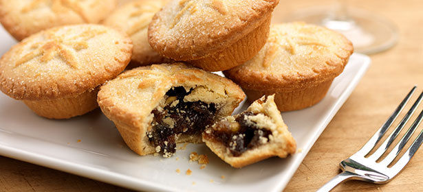 mince pies on a plate with one cut open to reveal mincemeat filling