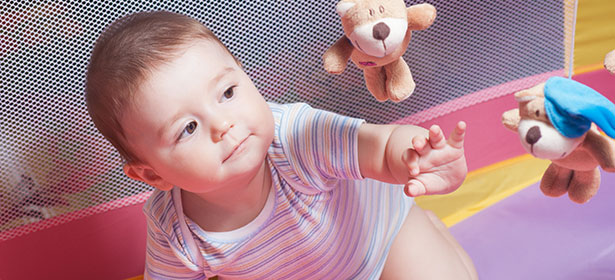 Baby playing in travel cot