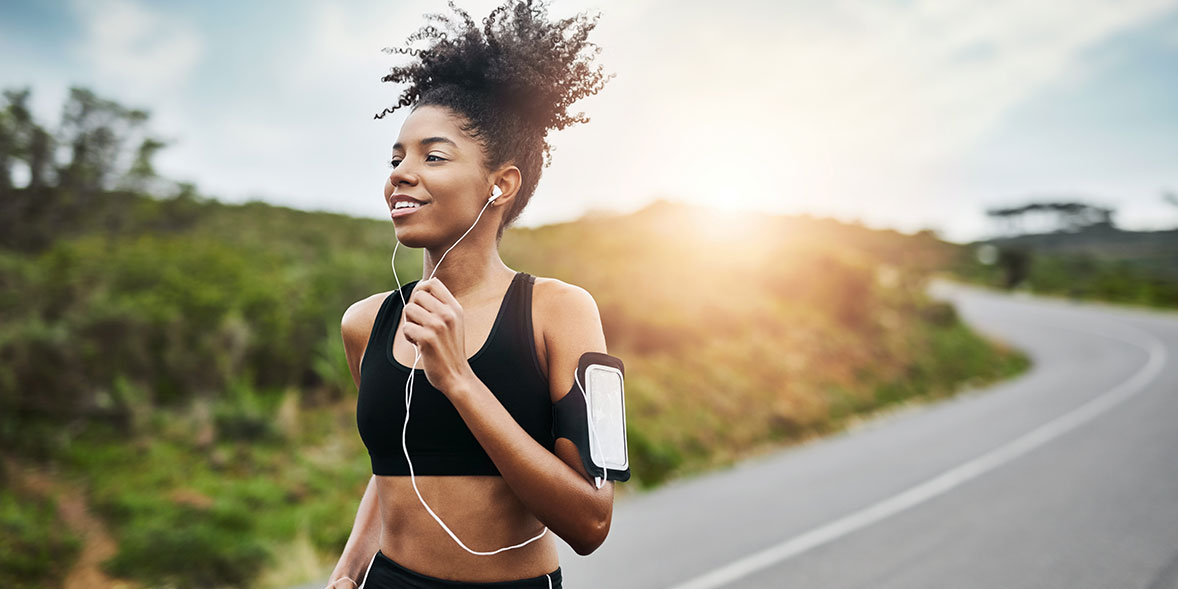 A woman running wearing a running armband and headphones