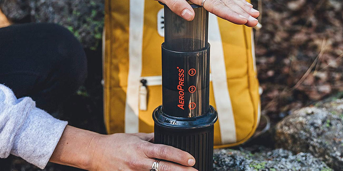 Person using an AeroPress on a hike