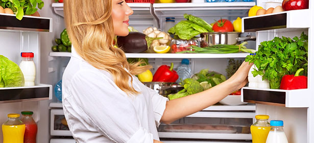 Woman looking at food in a fridge